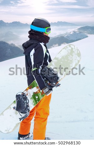 Female snowboarder  standing with snowboard in one hand and enjoying alpine mountain landscape - snowboarding concept #502968130
