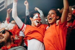 Female soccer fans in stadium celebrating victory. English spectators enjoying after a football championship win at stands