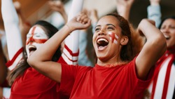 Female soccer fans of England watching and celebrating their team's victory. English female spectators enjoying after a win at stadium.