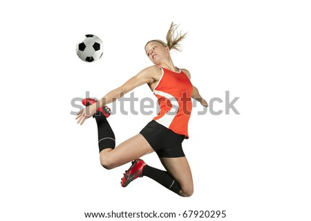 Female soccer player kicks a ball in mid air.