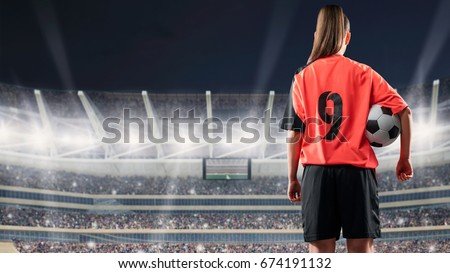 Shutterstock female soccer player standing with the ball against the crowded stadium at night
