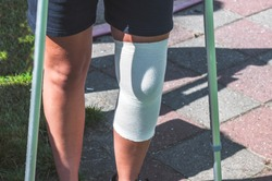 female soccer player stands on crutches the left leg connected with gauze bandage
