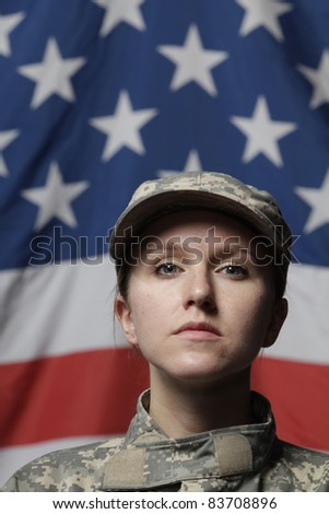 Female soldier in front of US flag - stock photo