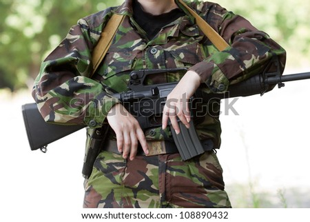 Female soldier with hands on her rifle