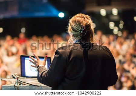 Female speaker giving a talk on corporate business conference. Unrecognizable people in audience at conference hall. Business and Entrepreneurship event.