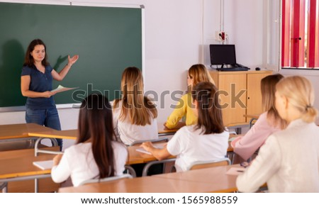 Female speaker giving lesson for university students in lecture hall #1565988559