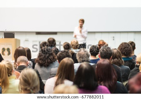 Female speaker giving presentation in lecture hall at university workshop. Audience in conference hall. Rear view of unrecognized participant in audience. Scientific conference event.