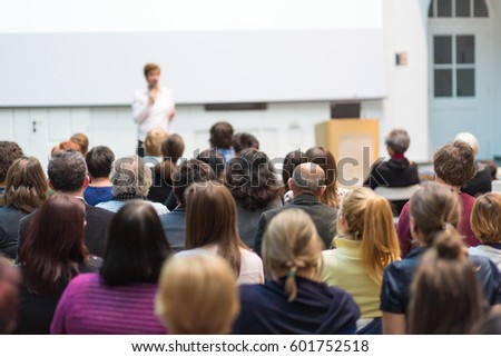 Female speaker giving presentation in lecture hall at university workshop. Audience in the conference hall. Rear view of unrecognized participant in audience. Scientific conference event. #601752518
