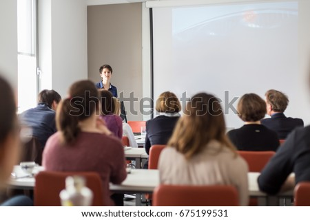 Female speaker giving presentation in lecture hall at university workshop . Participants listening to lecture and making notes. Scientific conference event. #675199531