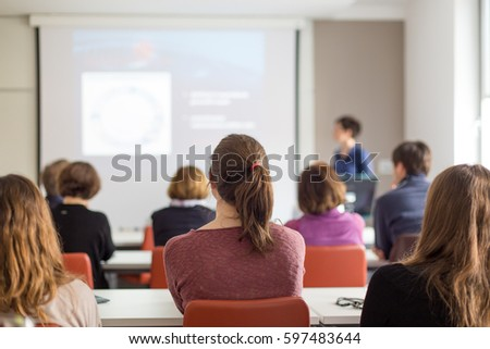 Female speaker giving presentation in lecture hall at university workshop. Rear view of unrecognized participants listening to lecture and making notes. Scientific conference event.