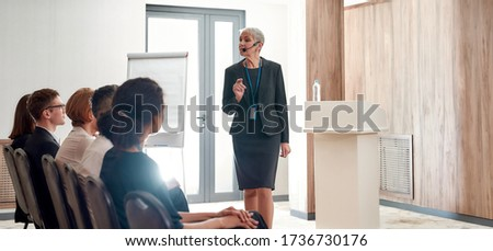 Female speaker in suit with headset giving a talk on corporate business meeting. Audience listening at conference hall. Business and Entrepreneurship event. Horizontal shot. Web Banner Stock photo ©