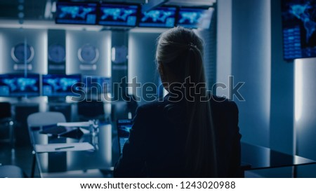 Female Special Agent Works on a Laptop in the Background Special Agent in Charge Talks To Military Man in Monitoring Room. In the Background Busy System Control Center with Monitors Showing Data Flow. #1243020988