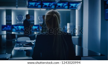 Female Special Agent Works on a Laptop in the Background Special Agent in Charge Talks To Military Man in Monitoring Room. In the Background Busy System Control Center with Monitors Showing Data Flow. #1243020994
