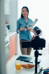 Female specialist having a camera with microphone on a tripod and gesturing while being recorded on a video