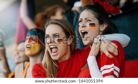 Female spectators cheering at sports event. Germany football team supporters actively cheering and chanting in crowd.