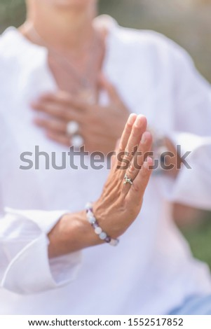 Female spiritual healer practicing mindfulness, sensing and increasing positive energy. Hand gesture