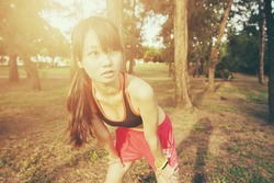 Female sport fitness runner getting ready for jogging outdoors on forest