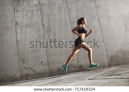 Female sport runner striving into bright future. Fit body requires hard work. Urban sport concept.