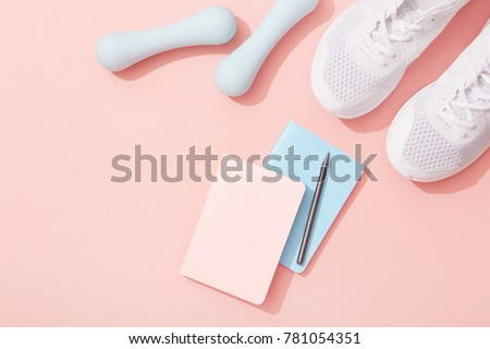 Female sports flat lay, dumbbells, notepad, sneakers on pink background, New Year fitness resolutions #781054351