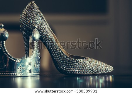 Female sprakling glamour luxury shoe on high heel and silver crown on reflecting table top close, glamour fashion concept, horizontal picture