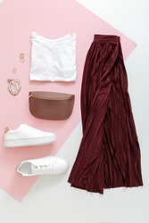 Female spring look summer outfit burgundy skirt white shoes sneakers white basic tshirt waist bag. Folded fly clothes for women fashion urban basic outfit with accessories on pink background. Top view