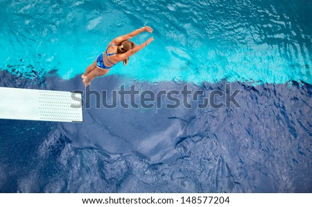 Female springboard diver diving into the swimming pool