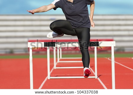 Female sprinter leaps over hurdle