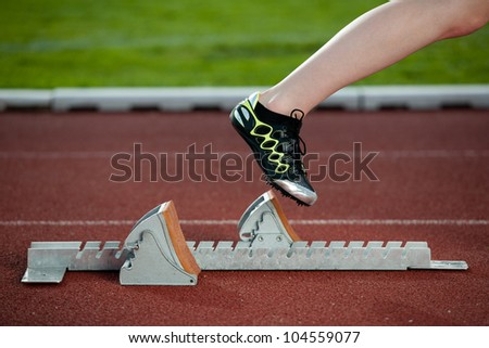 Female sprinter leaving the starting blocks for a sprint run on a track