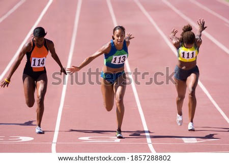 Female sprinters crossing the finish line at the end of a sprint race on a bright, sunny day at the track Stock photo ©