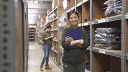 female staff in warehouse office look to camera with clipboard in hands. smiling girl worker in rows of shelves in stockroom. coworker in back concentrated working and counting stocks with tablet.
