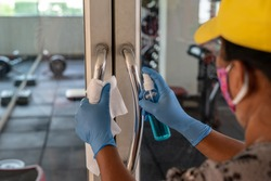 Female Staff using wet wipe and alcohol sanitizer spray to clean the door handle. Antiseptic,disinfection ,cleanliness and heathcare, anti virus concept. Anti Corona virus (COVID-19). Selective focus.