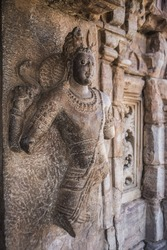 female statue in temple built by ancient civilizations. An extraordinary artwork made of stone. young woman has tired facial expression. Jewelries on the woman. Pattaya, Thailand.