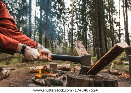 Female strong hands chop firewood with axe for bonfire. Powerful ax blow. Survival on camping trip. Harvesting wood in forest. Camp wild tourists. Splitting logs with sharp hatchet. Young woodcutter Foto stock ©