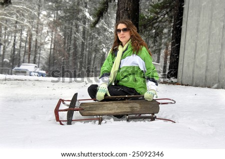 Female struggles with an old fashioned wooden sled as she kneels in snow.  Lime green jacket, gloves and scarf.