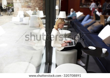 Female student connecting to wireless via laptop computer while sitting in modern coffee shop or university library, modern business woman keyboarding on net-book while working in loft studio interior