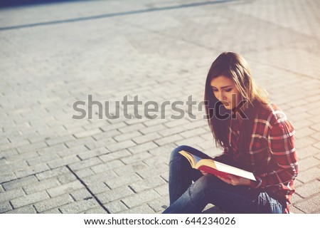 Female student enjoying interesting literature poem while sitting in urban setting in sunny day. Young casual dressed hipster girl relaxing outdoors while read an absorbing novel