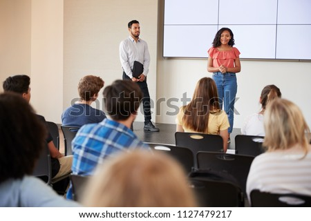 Female Student Giving Presentation To High School Class In Front Of Screen