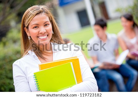 Female student holding notebooks and looking very happy