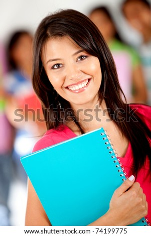 Female student holding notebooks with a group behind