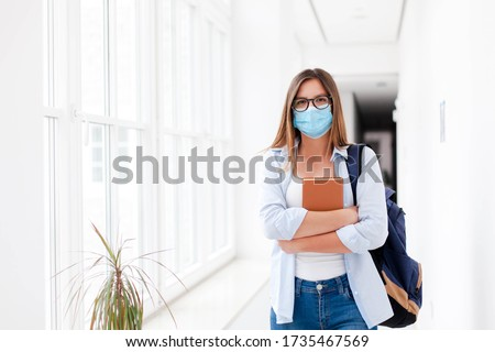 Photo of  Female student in mask indoors going to exams in high school. Young woman in empty university. Girl with backpack and book in college corridor. Social distancing during quarantine.