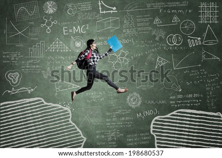 Female student jumping in classroom through gap on the blackboard