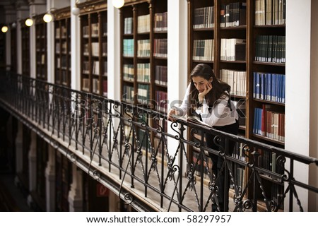 Female student leaning at handrail in old library reading a book; bookshelf with old books collection in background.