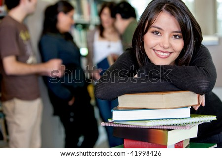 Female student leaning on books at the library with her friends behind