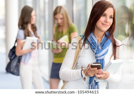 Female student listening mp3 player in high school hall - stock photo