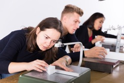 Female student of architecture faculty using scroll saw while engaged in architectural modeling in university workshop