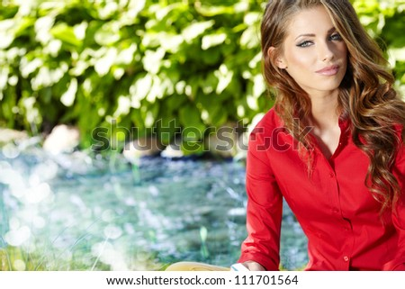 female student outdoor on green grass with book