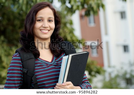 Female student outdoors holding  text books