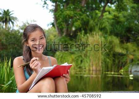 Female student outdoors in the campus park studying and taking notes. Beautiful smiling mixed race caucasian / chinese young woman model.