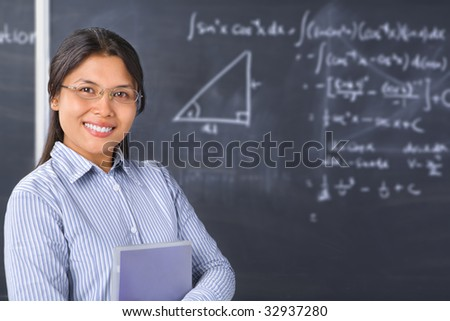Female student pose in front of blackboard