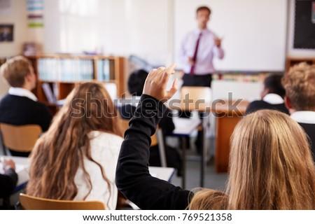 female student raising hand to...